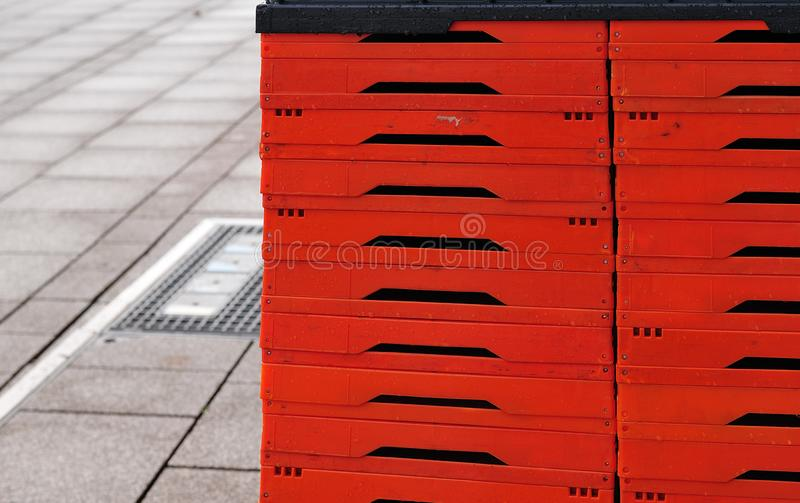 Red foldable plastic boxes on sidewalk. Stack of red foldable plastic boxes on sidewalk in a city royalty free stock images