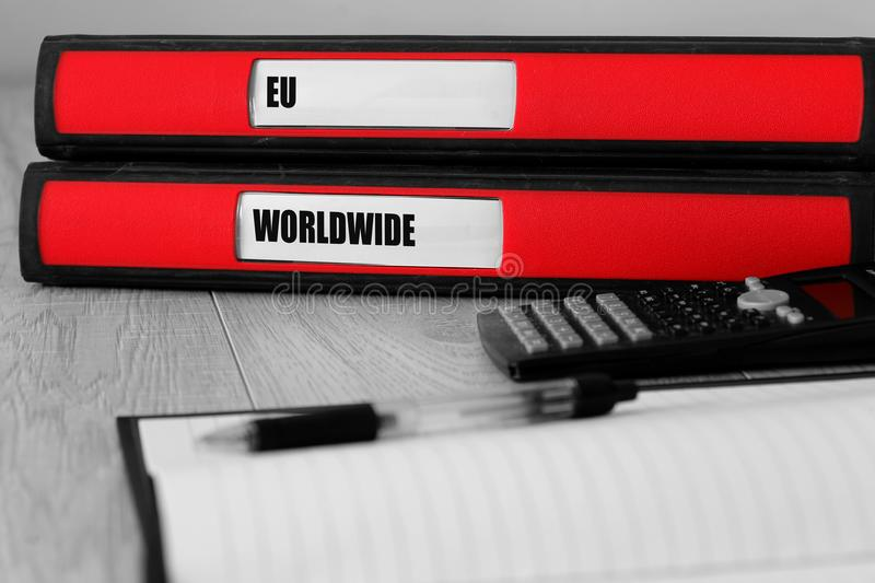 Red folders with EU and worldwide written on the label on a desk stock image