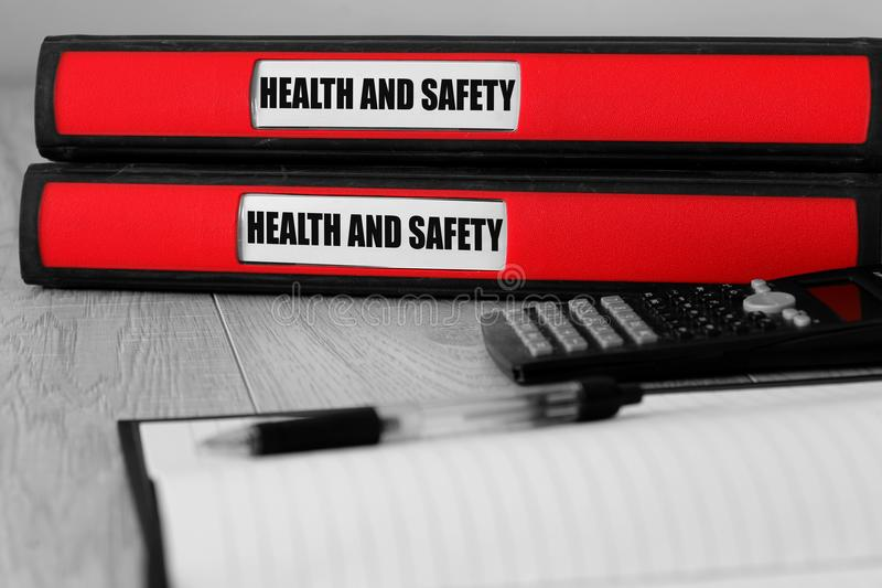 Red folders with health and safety written on the label on a desk. With selective colour royalty free stock photos