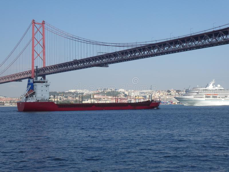 A red freighter and a liner under the bridge of April 25 in Lisbon, Portugal, Europe stock photos
