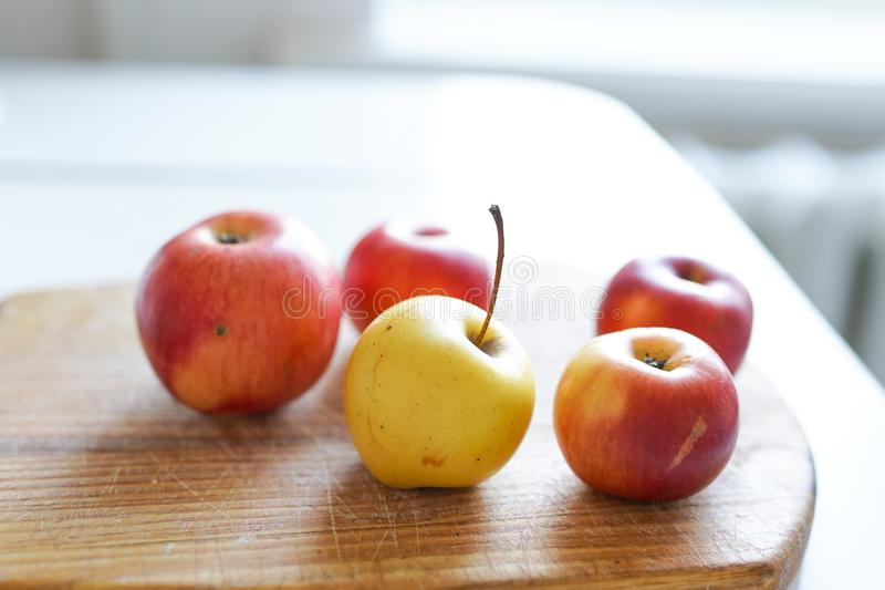 Red fresh apples on old wooden board on light background in white kitchen. healthy food stock images