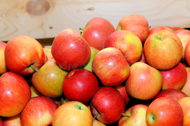 Red fresh apples in a pile on a wooden box royalty free stock photography