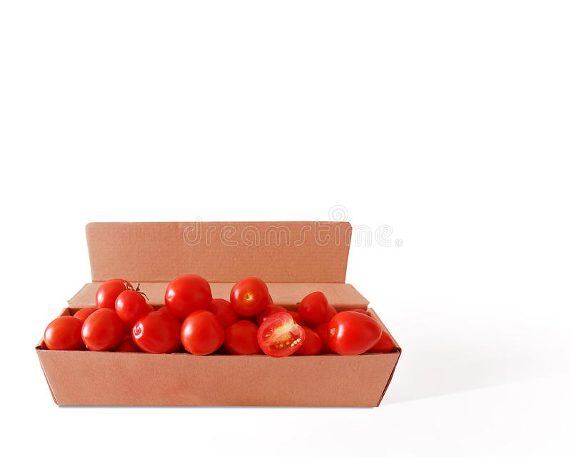Red fresh cherry tomatoes in a cardboard box. Isolate on white background. stock photography