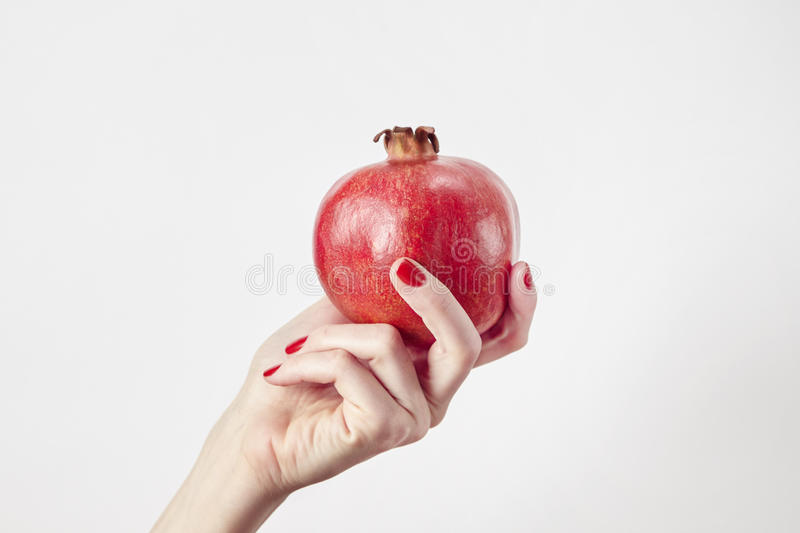 Red fresh pomegranate in woman`s hand isolated on white. Vegetables and fruits summer concept. Red fresh pomegranate in woman`s hand isolated on white royalty free stock image