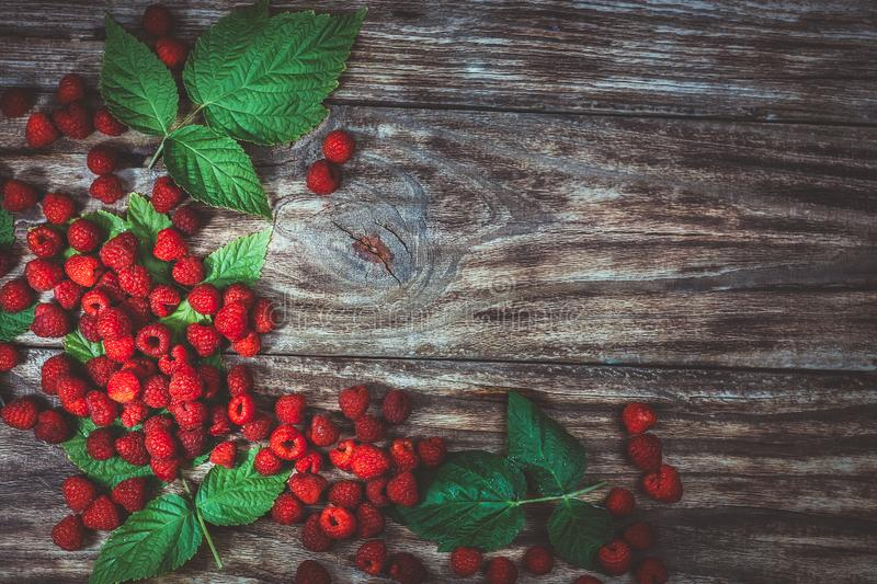 Red fresh raspberries on brown rustic wood background. stock photography