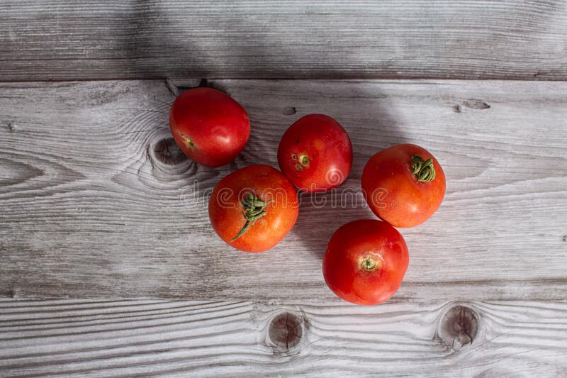 Red fresh raw tomatoes on a wooden board royalty free stock photos