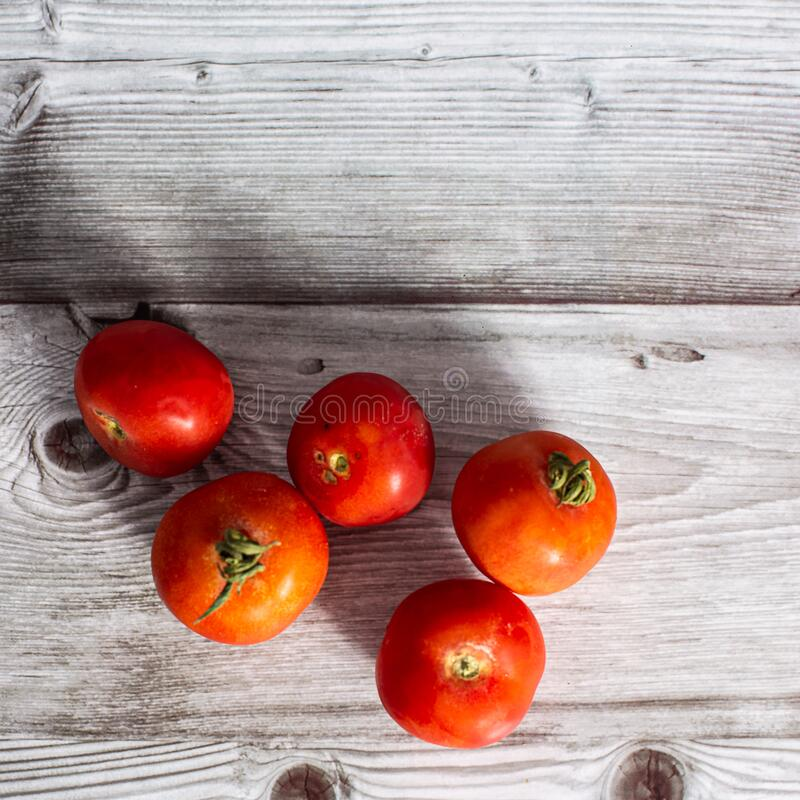 Red fresh raw tomatoes on a wooden board stock images