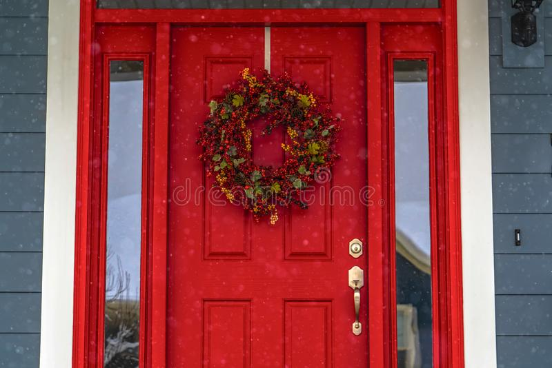 Red front door with wreath and glass panes in Utah. Vibrant red front door decorated with a colorful wreath in Daybreak, Utah. The snowy outdoors is reflected royalty free stock photography