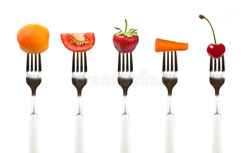 Red fruits and vegetables on the collection of forks stock photography