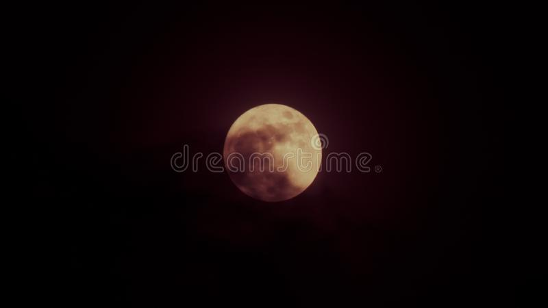 Red full moon behind shadow of cloud in dark sky night time.  stock images