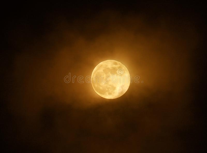Red full super moon glowing against clouds in a dark sky stock images