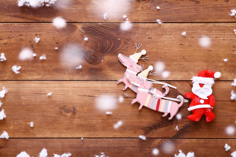 Santa claus riding Christmas sledge with deers on brown wooden background, xmas present gift sale, top view, copy space royalty free stock image