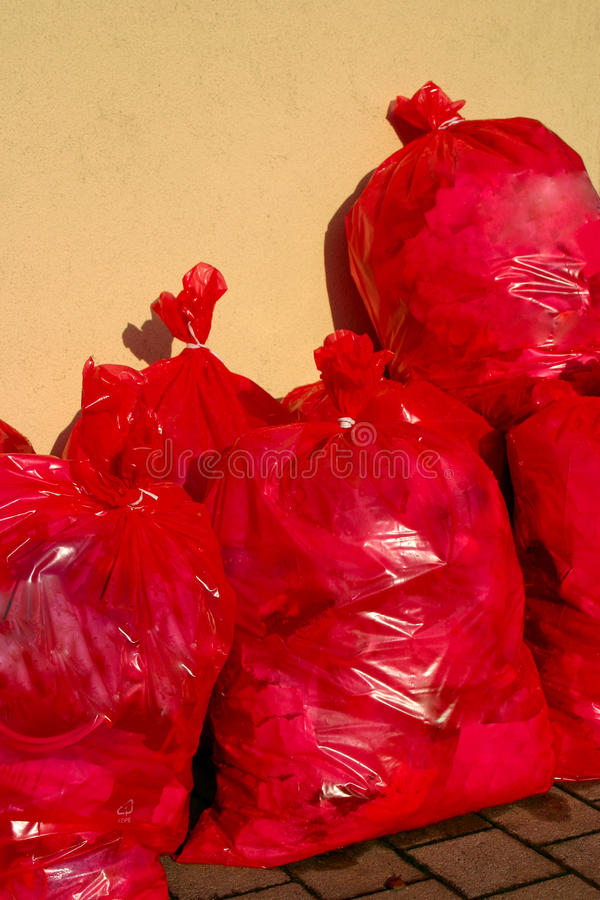 Red Garbage Bags. Group of Red garbage bags in front of a yellow wall royalty free stock photo