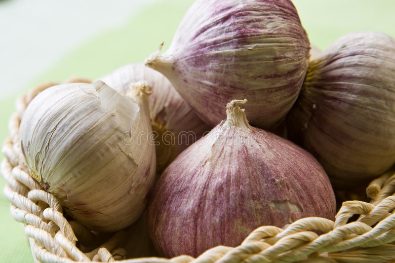 Red garlic cloves. In a basket royalty free stock image