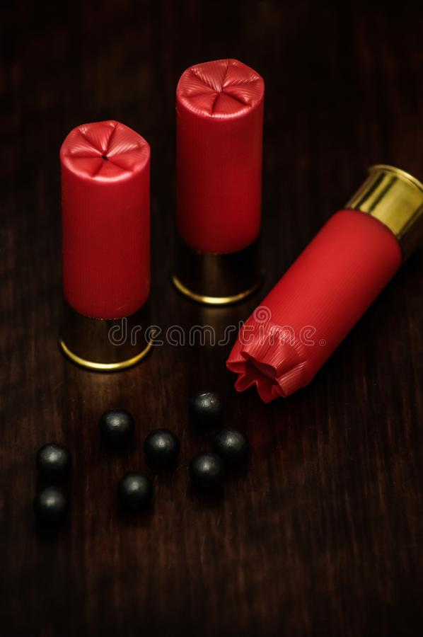 Red shotgun shells on a wooden surface stock image