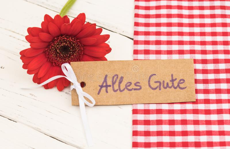 Greeting card with german text, Alles Gute, means best wishes with red flower decoration royalty free stock image
