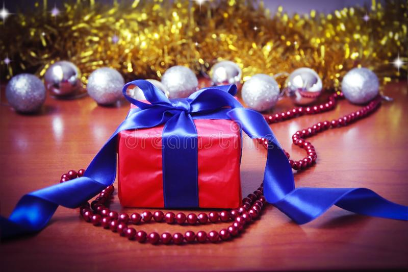 Red gift box with blue bow on the background of Christmas toys for the new year holiday royalty free stock photos
