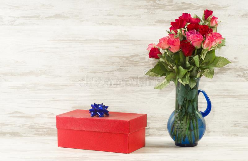 Red gift box with a blue bow and roses on a background of vintage boards royalty free stock image