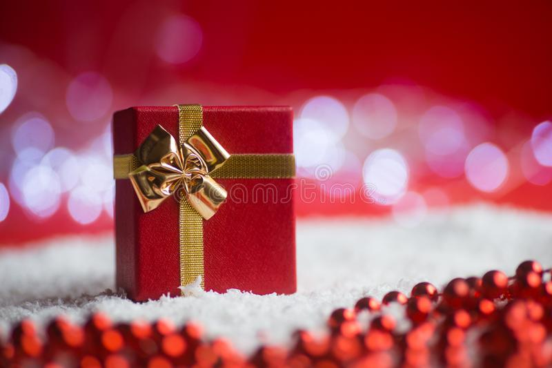 Red gift box with golden bow with beads on snow on festive bokeh background stock image
