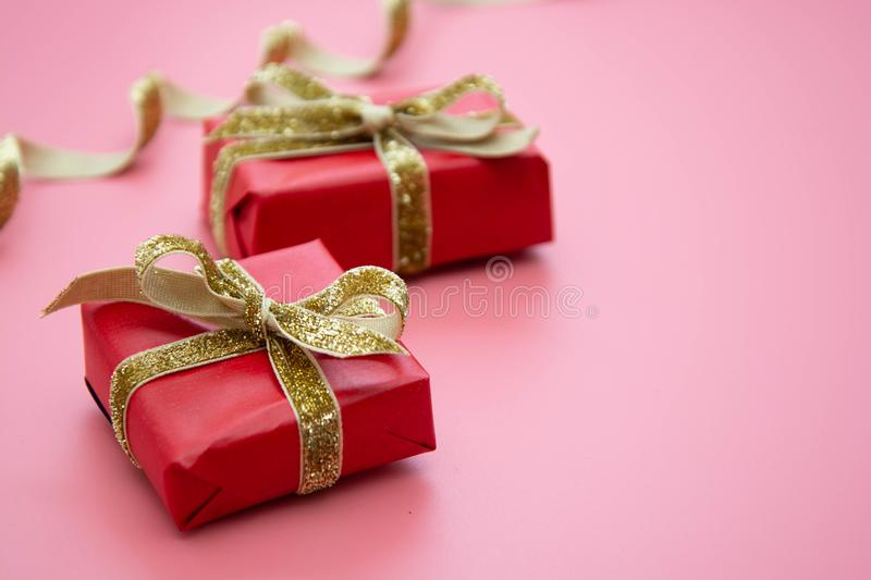 Red gift box and golden bow, on pink background. Valentine's Day, Birthday, Party concept. Mock up, sparkle, holiday, package, present, celebration royalty free stock photos