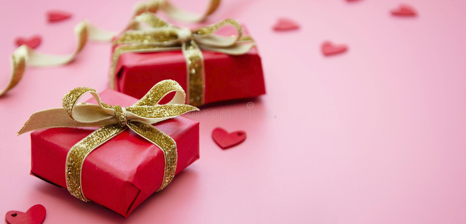 Red gift box and golden bow, on pink background. Valentine's Day, Birthday, Party concept. Mock up stock image