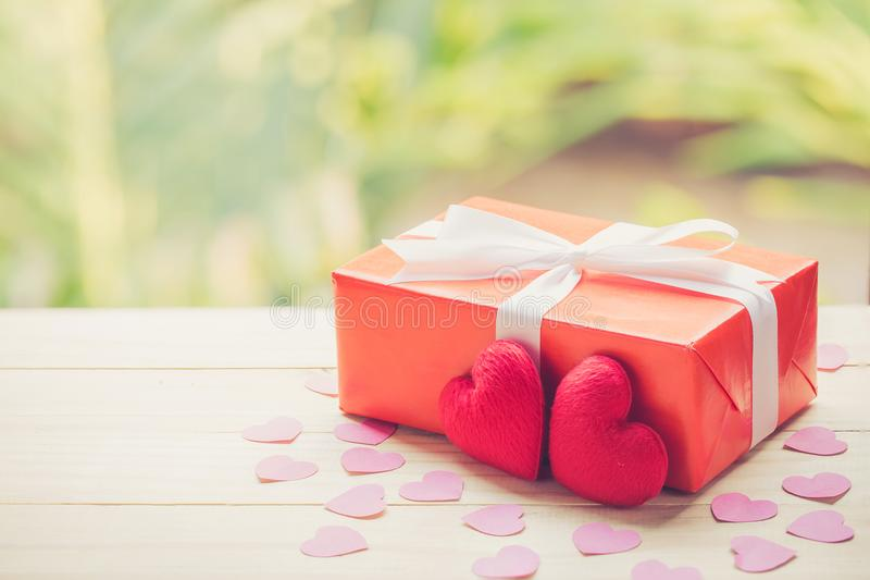 Red gift box and heart shape on wood table top with nature green blur bokeh background. royalty free stock photo