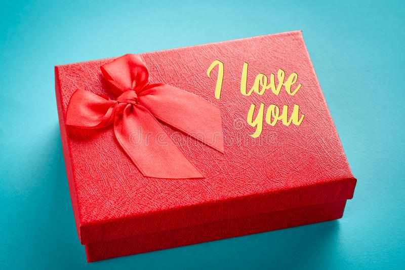 Red gift box with the inscription on the cover I love you on a blue background: concept of a romantic gift royalty free stock images