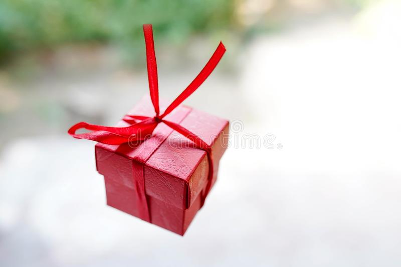 Red gift box on light background with copy space, surprise for birthday or valentine`s day stock image