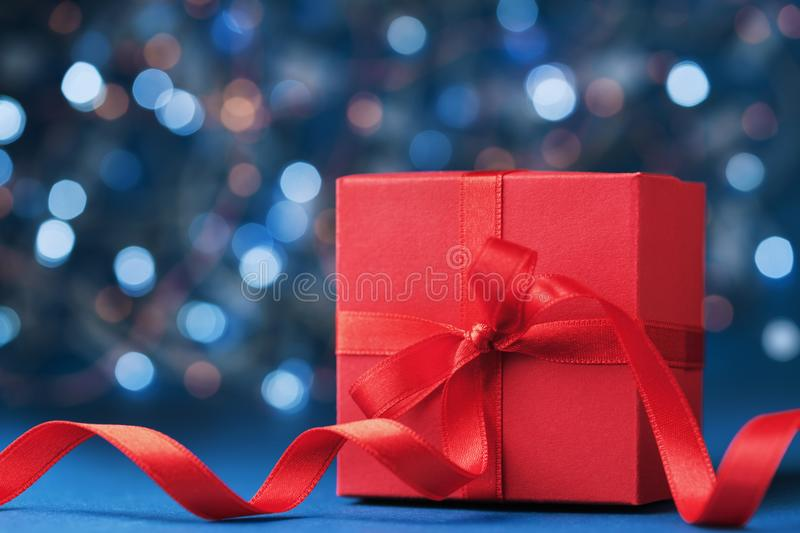 Red gift box or present with bow ribbon against blue bokeh background. Christmas greeting card. stock photo