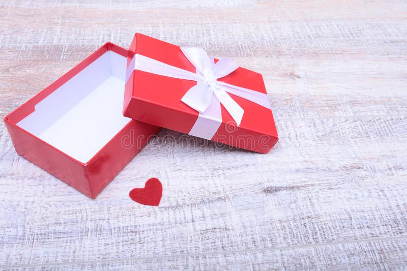 Red gift box with ribbon bow opened on vintage white wooden table stock photos