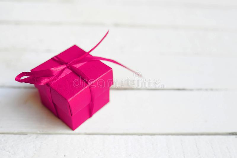Red gift box with ribbon on white wooden background. copy space stock photo