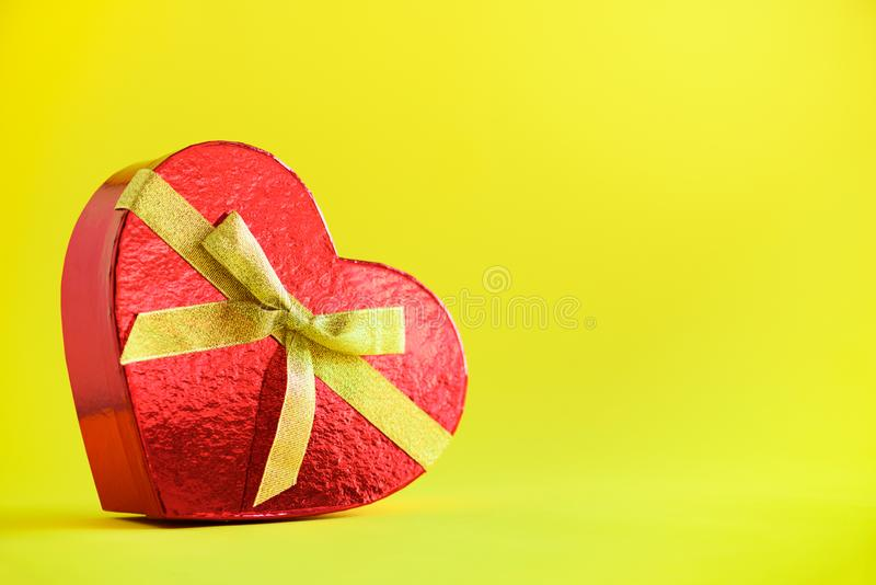 Red gift box in shape of heart on yellow background. Copyspace for text. Valentines day. Romantic love concept. Present for her stock image