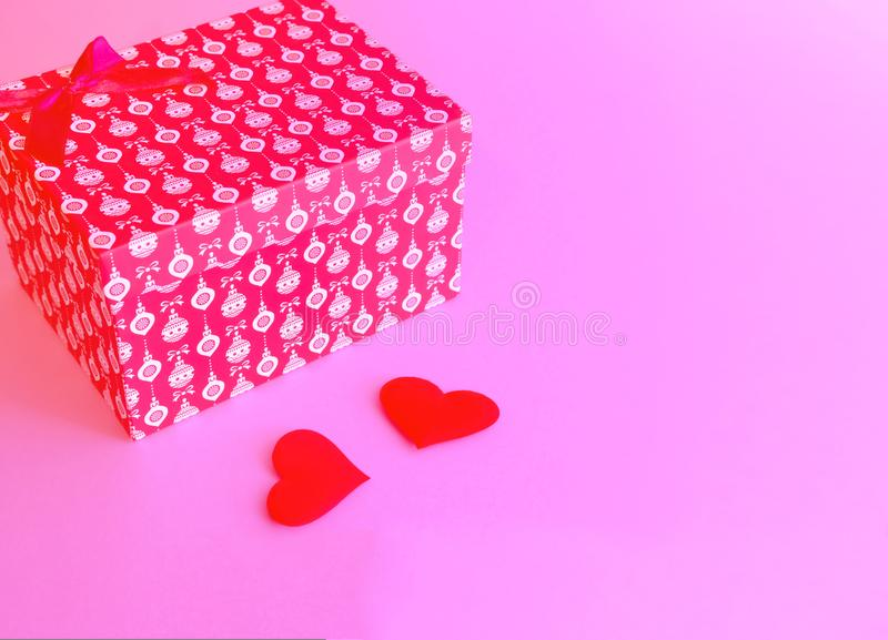 Red gift box tied with a red ribbon on a pink trendy background. royalty free stock image