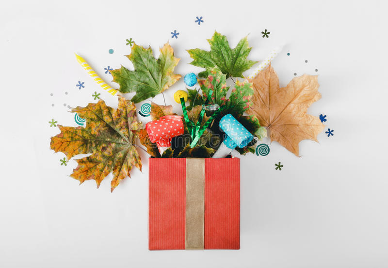 Red gift box with various colorful dry leaves, party confetti stock photo