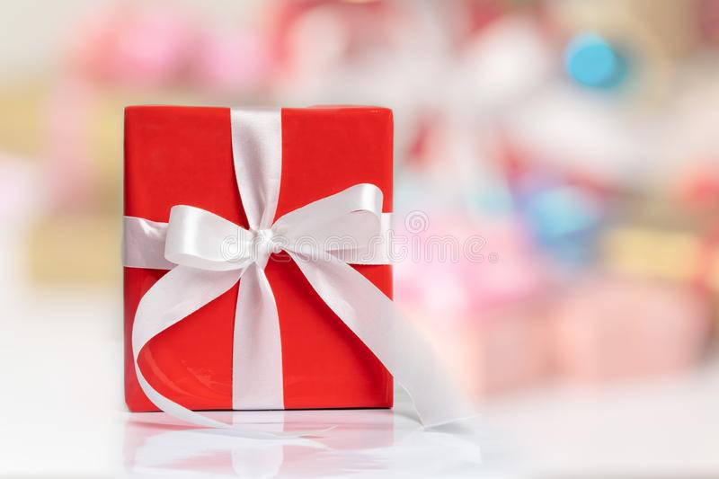 A red gift box with white ribbon on the table and blurred backgrounds for any holiday concept. With copy space. Surprise gifts for special occasions, tied stock photo