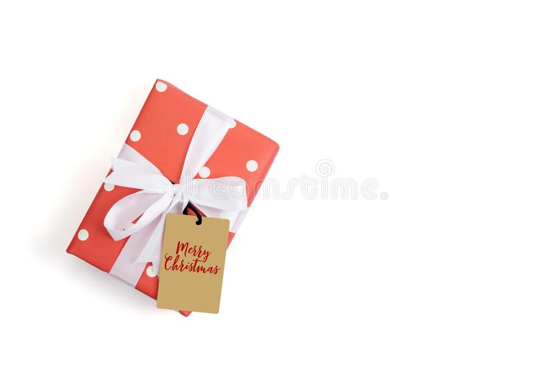 Red gift box and white ribbon with tag in season Christmas and new year isolated on white background royalty free stock photos