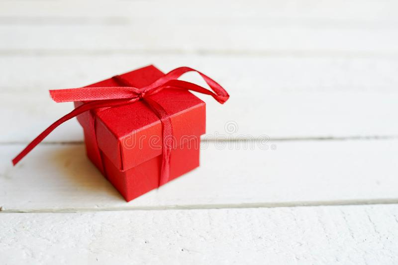Red gift box on white wooden background with copy space, surprise for birthday, christmas, or valentine`s day stock photos