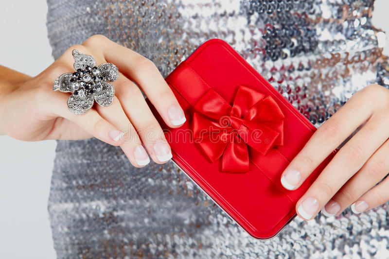 Red gift box in woman s hands.