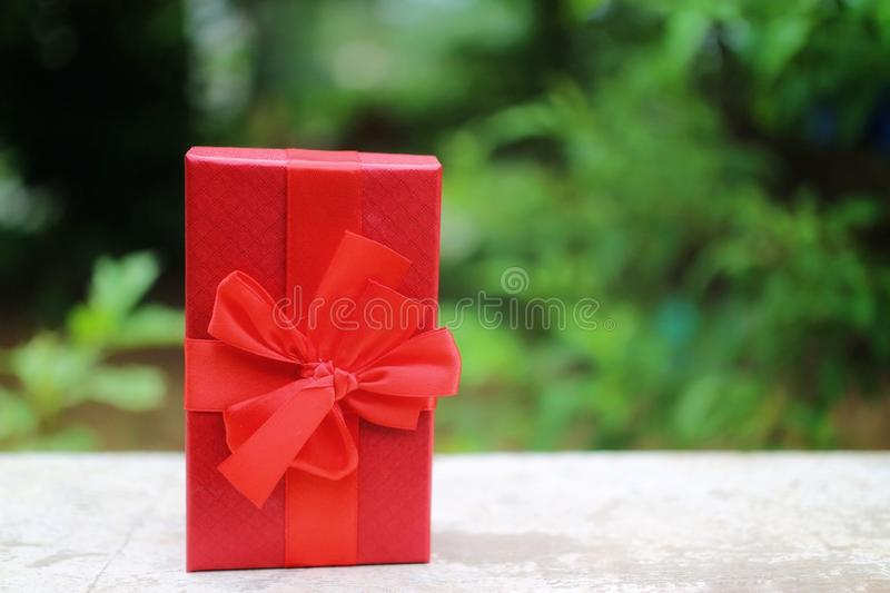 Red gift boxes and ribbons placed on wooden floors for Christmas and New Year or birthday, Valentine& x27;s Day. stock photo