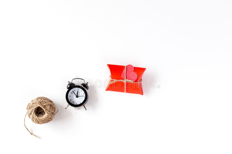 Red Gift Package, rope and Alarm clock on a white background. Handmade gift on white background. Time for Holiday Concept. stock photography
