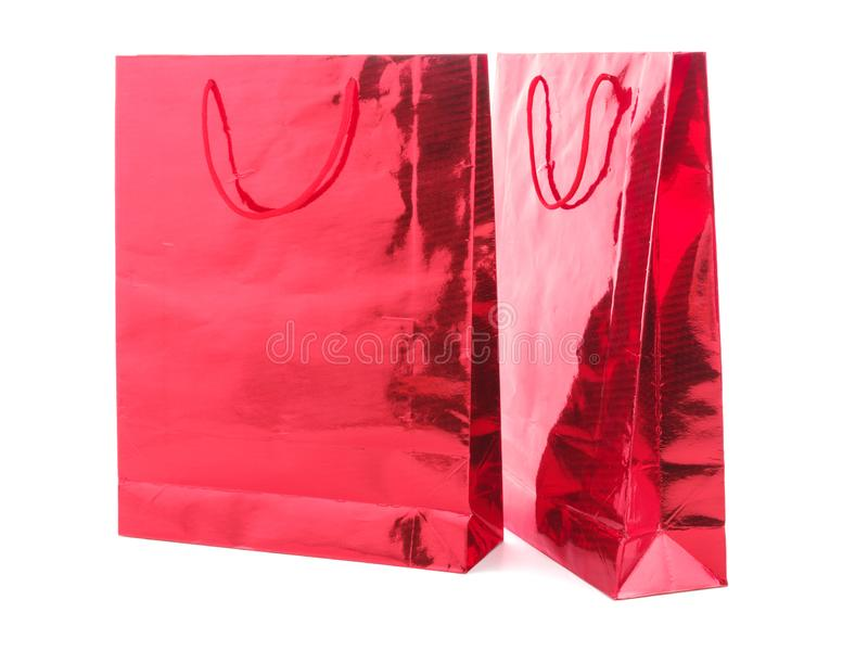 RED GIFT PACKAGE ON WHITE BACKGROUND. Colourful paper shopping bags isolated on white stock images