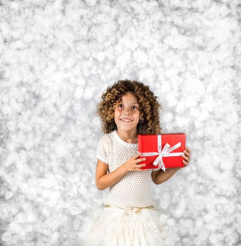 Red Gift. Picture of a little white caucasian girl with curly hair holding red gift box with white ribbon against bright white sil stock image
