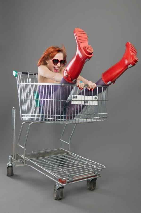 Red girl riding on a shopping cart stock photos
