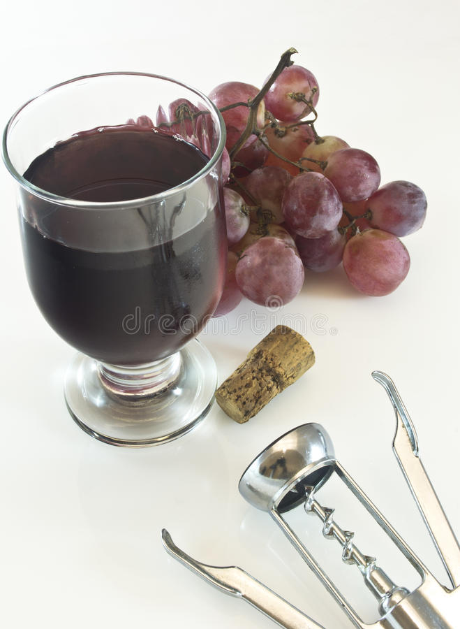 Red glass of wine. With grape, cork and corkscrew on white background stock photos