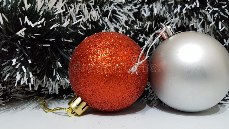 Red glitter christmas ball decoration with a silver ball decoration. Two christmas ball decorations, one with red glitter and the other with silver matte finish royalty free stock photos