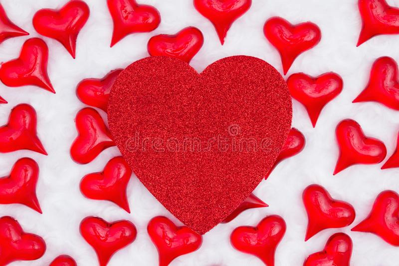 Red glitter heart with red hearts on white fabric background stock images