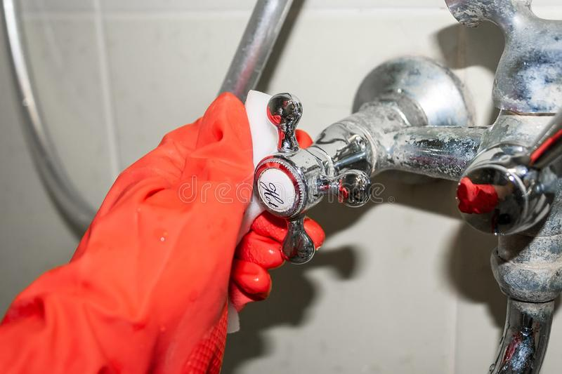 A red-gloved hand rubs a hot water knob on a chrome-plated faucet covered with limestone with a white melamine sponge. Selective focus. Closeup view stock images