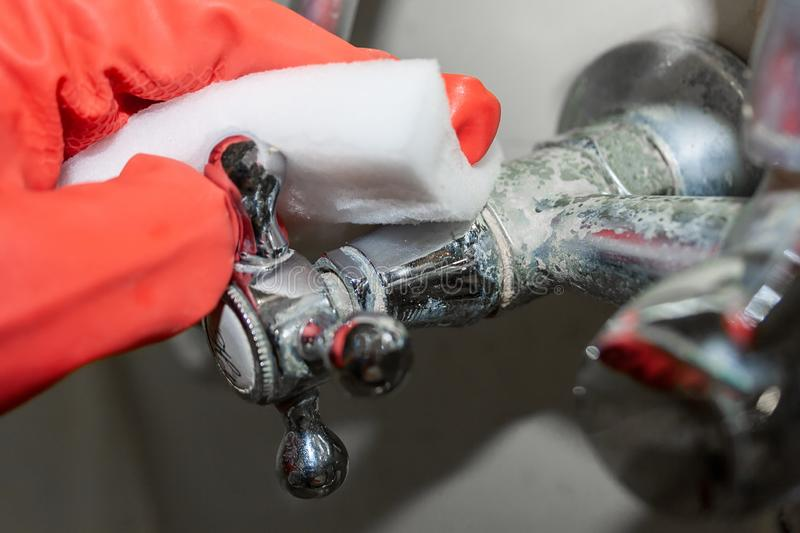 A red-gloved hand rubs a hot water knob on a chrome-plated faucet covered with limestone with a white melamine sponge. Selective focus. Closeup view royalty free stock image
