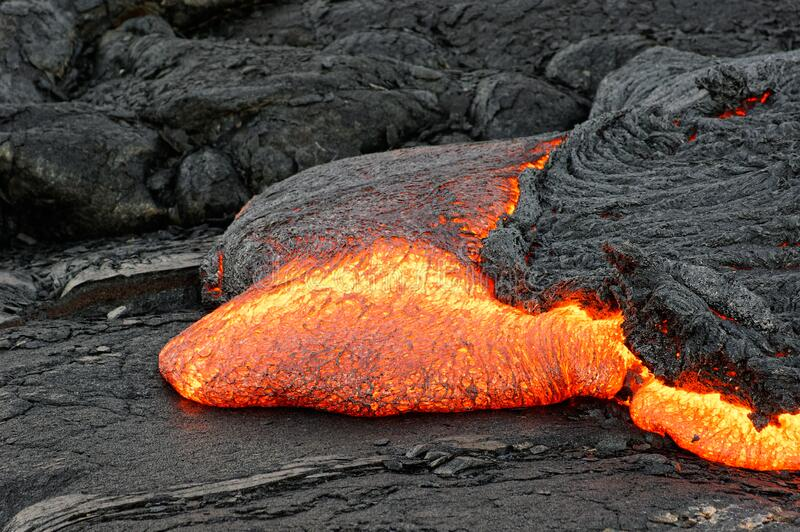 Red glowing lava flow on Hawaii stock image