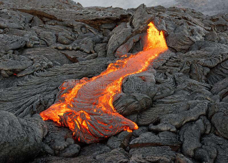 Red glowing lava flow on Hawaii stock images